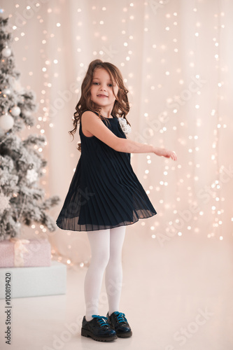 smiling baby girl 5 6 year old dancing in roomover christmas lights looking at - What To Get 6 Year Old Little Girl For Christmas