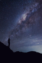 A person is standing next to the Milky Way galaxy thump up on a
