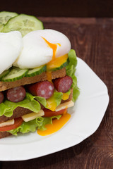 Sandwich with tomatoes, cucumbers, sausages, salad and poached eggs
