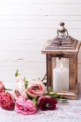 Background with flowers   in pink  colors and candle in lantern