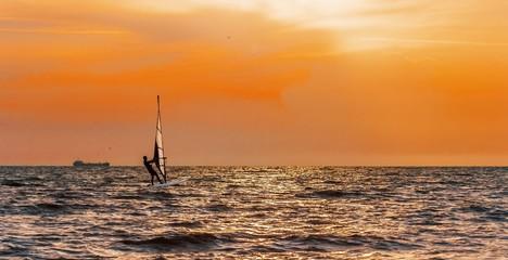 Windsurfing on orange sunset's background