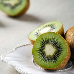 The kiwi fruits on the table on a white plate