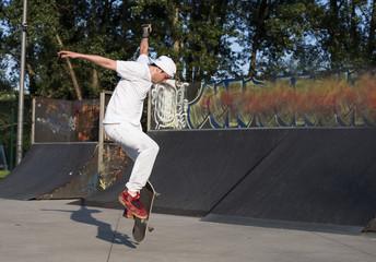 Skateboarder doing a jumping trick at skateboard park