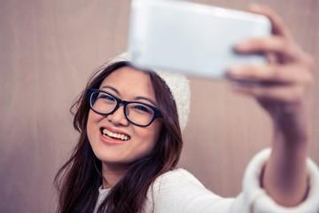 Smiling Asian woman taking selfie