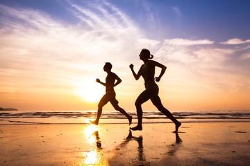 Fototapeta runners on the beach, sport and healthy lifestyle obraz