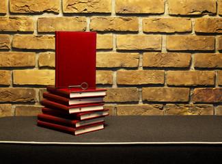 Książki na ławce na tle ściany z cegły.