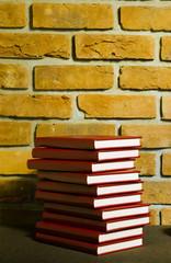 Książki w skórzanej oprawie na tle ściany z cegły.