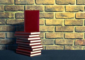 Książki w bordowej skórzanej oprawie na tle ściany z cegły.