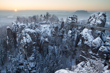 schneebedeckte Basteibrücke im winterlichen Elbsandsteingebirge