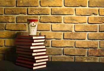 Książki i kubek na tle ściany z cegły.