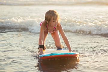 Little girl riding a boogie board in ocean