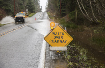 Emergency vehicle driving on flooded road with warning sign