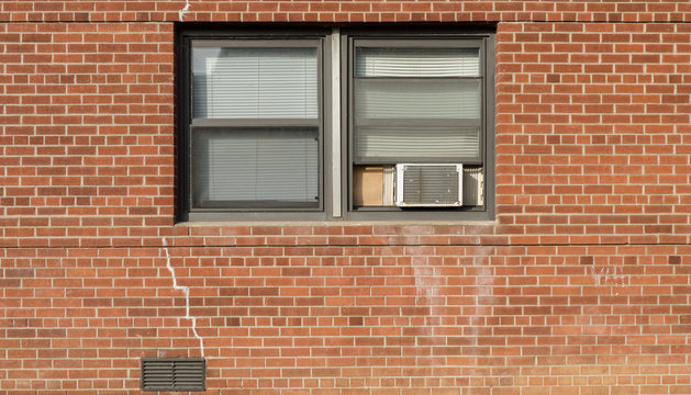 Window on brick red wall whith AC