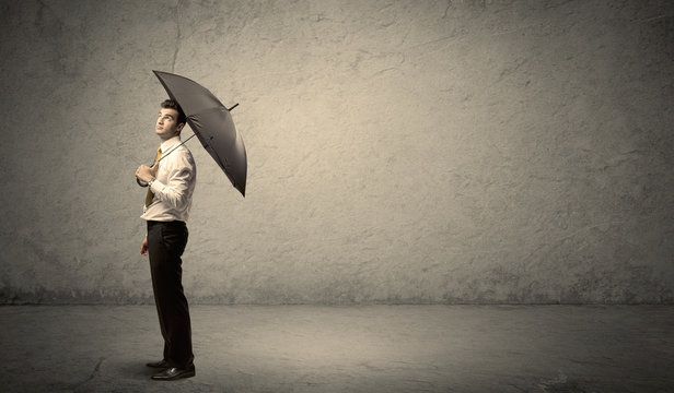 Handsome business man holding umbrella with copy space backgroun