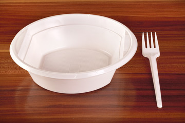white plastic plates and forks on table