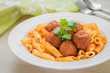 Penne pasta with meatballs in tomato sauce on plate