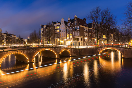 Night view over Amsterdam canals and bridges, with lights and their trails