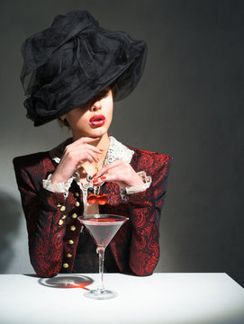 A woman in a vintage hat drinking a martini with a cherry