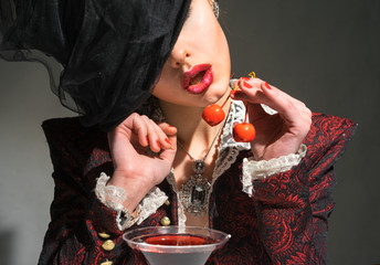 Woman drinking a martini with a cherry