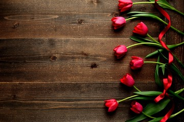 Red tulips with red ribbon on the black wooden background