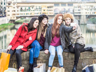 Four female friends taking a selfie on a bridge in Florence, Tuscany. Behind them the beautiful Ponte Vecchio. The women are dressed in winter jackets and hats against the cold of winter