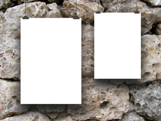Close-up of two hanged paper sheets with clips on stone wall background