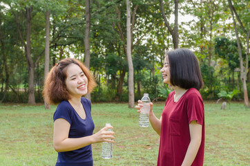 Two Asian girls drinking water after excercise