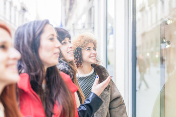 A group of four women friends view window of a shop in the city. A woman shows while others smile
