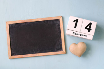 February 14th wooden vintage calendar and wooden heart next to blackboard on wooden light blue background. valentine's day celebration concept