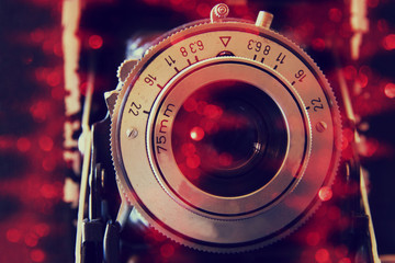 abstract photo of old camera lens with glitter overlay. image is retro filtered. selective focus