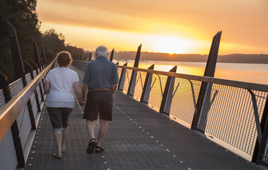 older couple walking at sunset