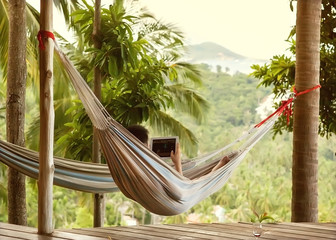 man lying in a hammock freelancer and running, beautiful mountai