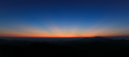 Panorama of colorful sky above mountain just before sunrise