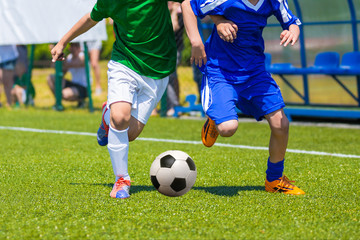Training and football match between youth soccer teams. Young boys playing soccer game. Players running and kicking soccer ball. Game of football tournament for kids. Running players in uniforms.