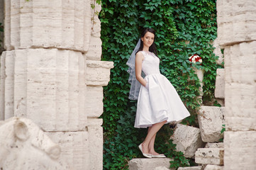 Young bride with wedding bouquet stands near a beautiful old wall