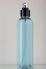 Flacone in plastica trasparente con liquido azzurro e spruzzatore nero