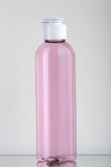Flacone in plastica trasparente con liquido rosa e tappo bianco