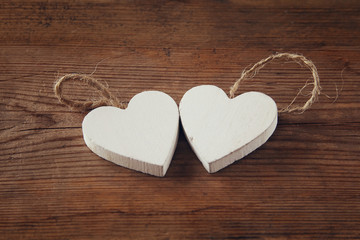selective focus photo of couple of wooden hearts on rustic table.  valentine's day celebration concept. vintage filtered