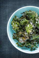 Kale chips with salt in pastel blue bowl captured from above (top view). Healthy dietetic snack. Black chalkboard as background.