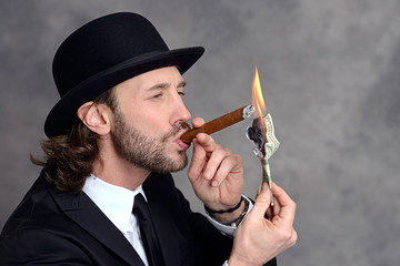 businessman with bowler hat lighting big cigar with money