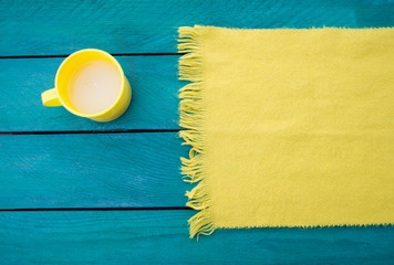 Mug of milk and yellow scarf on a turquoise surface