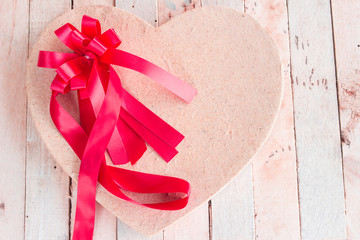 Red ribbons and  paper hearts on a wooden background. Valentine day concept