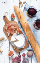 Camembert cheese, prosciutto (italian ham), baguette, two glasses of red wine, figs and grapes. White wooden table as background. Romantic french picnic scenery captured from above (top view).