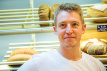 smiling man selling bread in a bakery