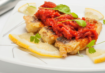 Pieces of fried fish with vegetable marinade.