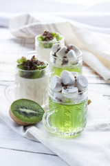 Jelly with kiwi fruit with marshmallows and grated chocolate in glass, sliced kiwi on white wooden table