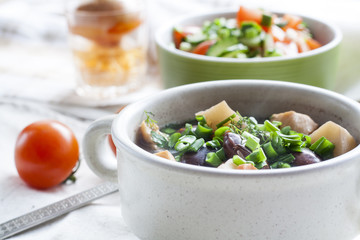 Vegetable soup with beans and chicken, fresh herbs in a clay pot, salad of tomatoes and cucumbers with greens in a green bowl on a white wooden table.