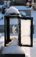 close photo of old open lantern on the grave in winter