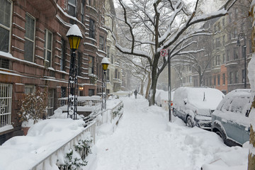 Snow covered street with Brownstone apartment buildings near Central Park during snowstorm in New York City
