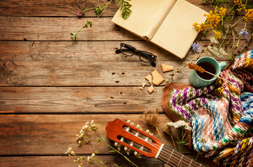Late summer or autumn relaxation, rustic background on wood from above. Country lifestyle, rural vacation or agrotourism concept. Layout with free text space. Book, blanket, coffee and guitar.